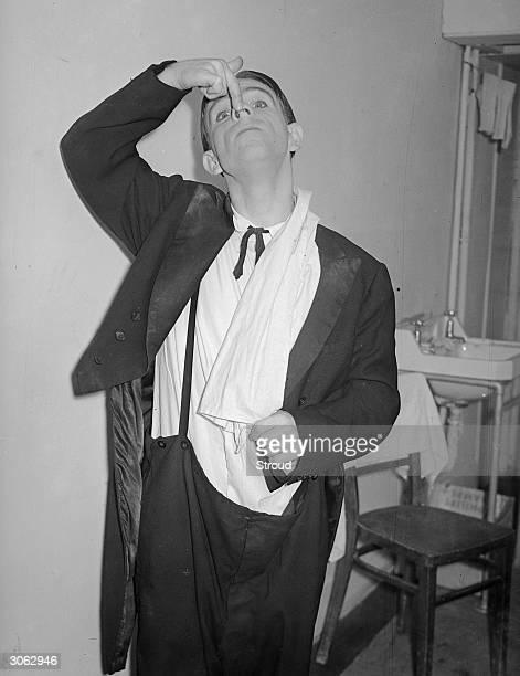 English slapstick comedian Norman Wisdom having trouble with his attire