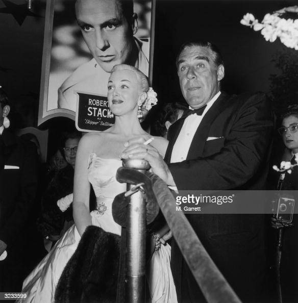 EXCLUSIVE Married American actors Jan Sterling wearing a pale strapless evening gown and Paul Douglas smoking a cigar in a tuxedo stand in the lobby...
