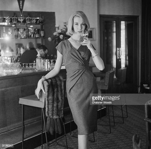 An elegant lady with sable draped over bar stool enjoys a naughty little glass of Chardonnay wine