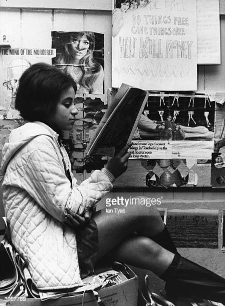 A young shop assistant reads a book at the back of the shop