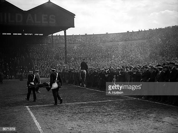 Ambulancemen carry one of the many casualties from the huge crowd off the pitch at Old Trafford before the start of the FA Cup SemiFinal match...