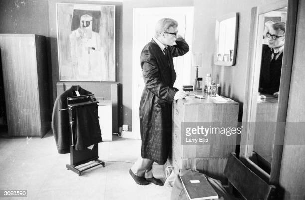 Clad in a dressing gown while his suit hangs on the trouserpress British actor Michael Caine examines his reflection in the mirror