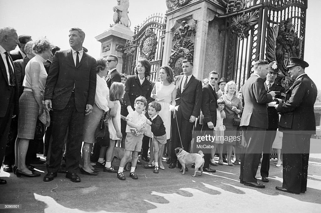 Jackie Kennedy, widow of president John F. Kennedy, standing outside Buckingham Palace during a visit to London with her children John Jr. (1960 - 1999) and Caroline, her sister Lee Radziwill and Lee's son Anthony.