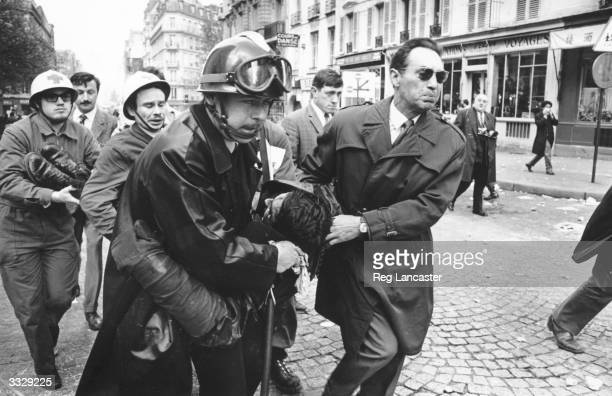 A man is carried by both Police Medics during the Paris riots