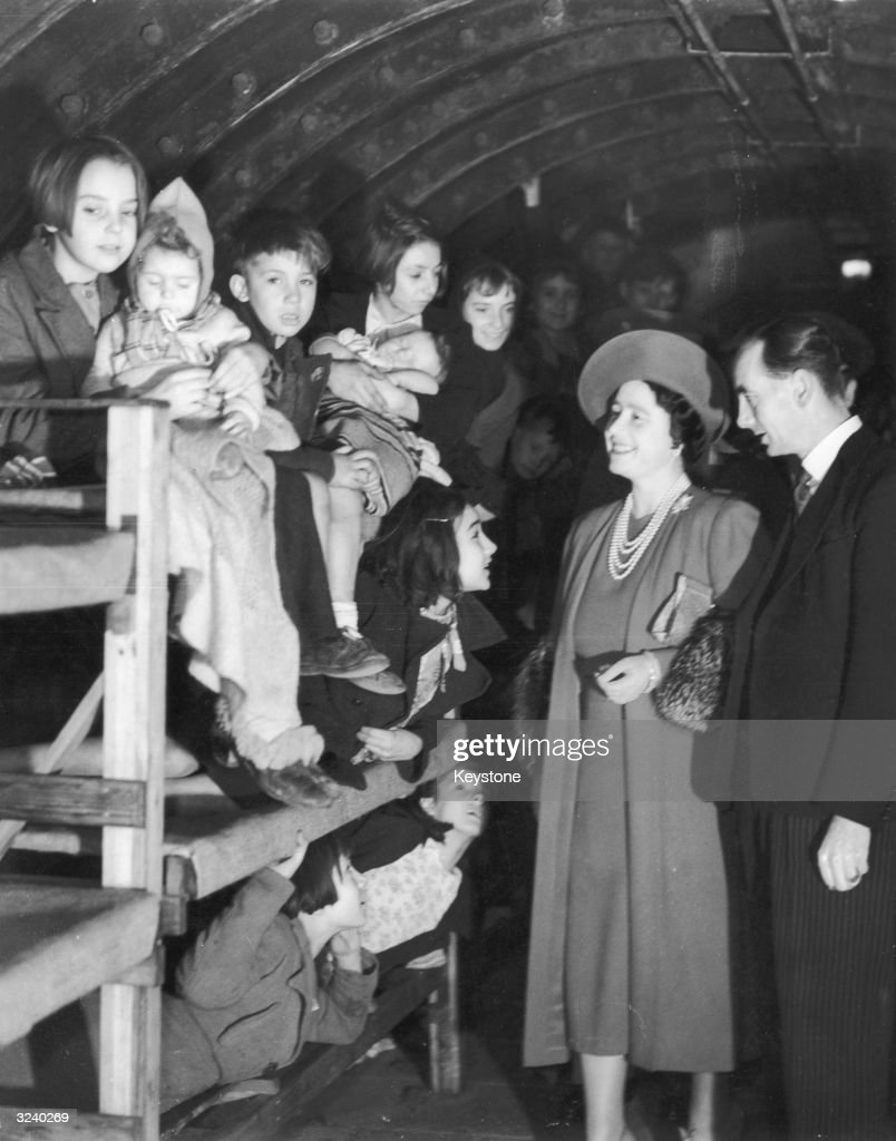 Queen Elizabeth (1900 - 2002) beaming at children in their bunks during a visit to an air raid shelter in London.