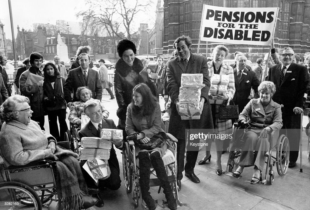 A delegation for the disabled petitions for higher incomes and pensions. Receiving the petitions are Mr Jack Ashley (left) and Mr John Pardoe.