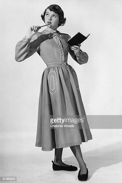 A woman modelling a rather dowdy Brilkie dress with white piping and flat shoes