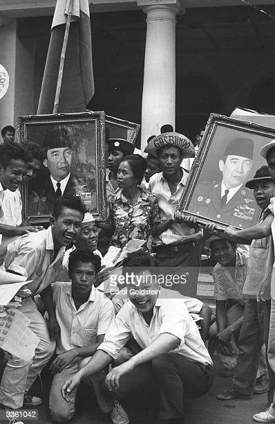 Muslim youths with pictures of Indonesian president Sukarno which they took during a raid on a communist book store
