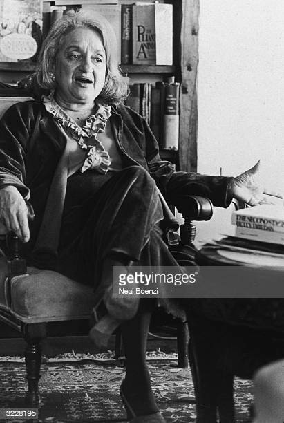American author and feminist leader Betty Friedan talks and gestures with her hands while sitting in front of a bookcase in her apartment New York...