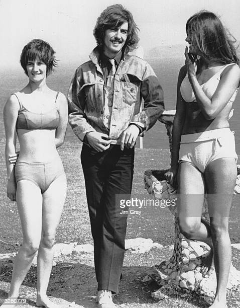 George Harrison of pop group the Beatles talks to 17 year old Catherine Osbourne of Stanstead Abbots Hertfordshire and her friend who are on holiday...
