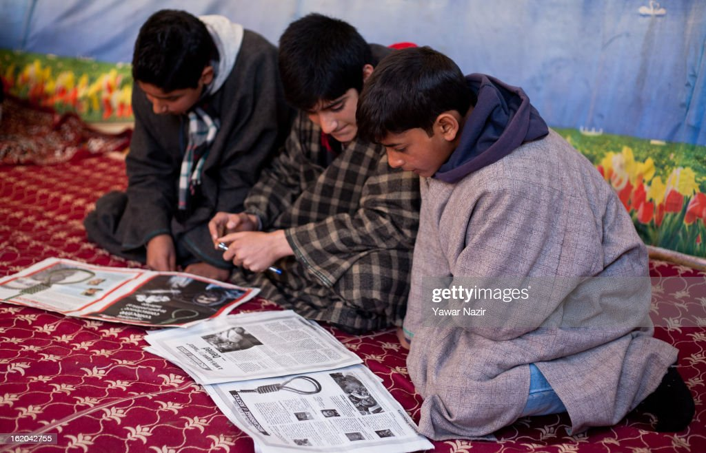 14-year-old Ghalib Afzal Guru, the son of executed Kashmiri separatist Afzal Guru, reads a newspaper with his cousins at his residence on February 18, 2013 in Jagir, Sopore, 50 km (31 miles) north of Srinagar, the summer capital of Indian-administered Kashmir, India. Guru was secretly hanged and buried at the Tihar Jail in India's capital, New Delhi, on February 9 for his alleged role in the 2001 attack on the country's Parliament. His family alleges that they were kept in dark about the execution by the Indian government . Apprehensive of a massive public fallout over the execution, Indian authorities clamped a curfew for seven consecutive days in Kashmir even as three people were killed allegedly in Indian government forces' action during protests and clashes . Meanwhile, separatist groups have called for a three day strike beginning Wednesday to press the Indian government for handing over of Guru's mortal remains to his family for his last rites, a demand growing louder by the day in Kashmir.