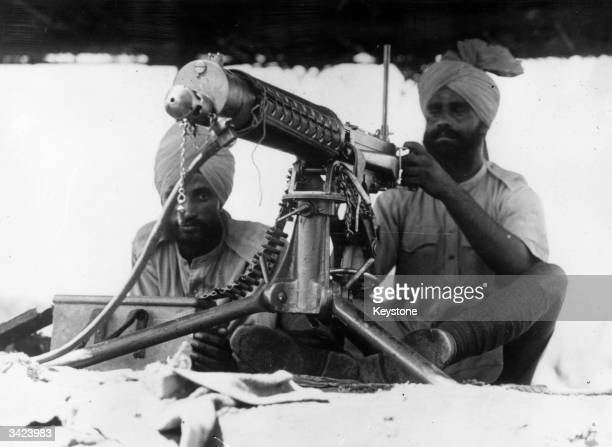 Two Indian gunners contributing their services to the Allied Army at their machine gun in the Libyan desert