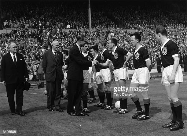 Prince Philip Duke of Edinburgh shaking hands with Ian St John before England play Scotland at Wembley Denis Law is on Ian St John's right Law was...