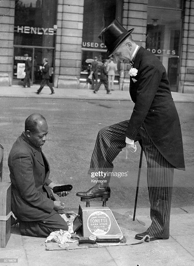 Captain J A Paton getting his shoes cleaned by a bootblack in Piccadilly, London, before going to Ascot races.