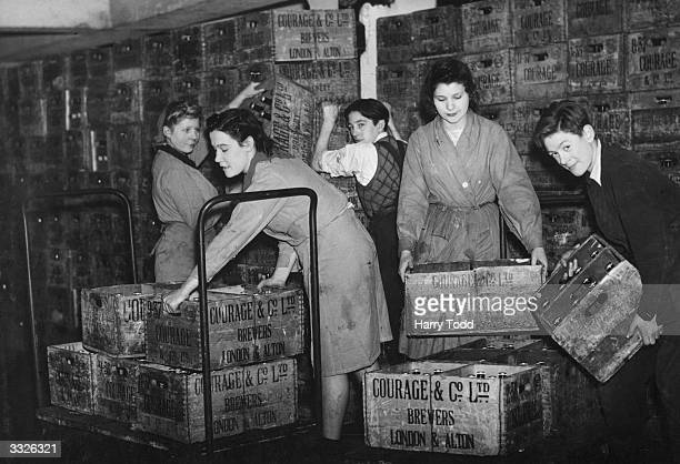 Workers at the Horsleydown Brewery stacking crates of beer onto trolleys in preparation for Christmas