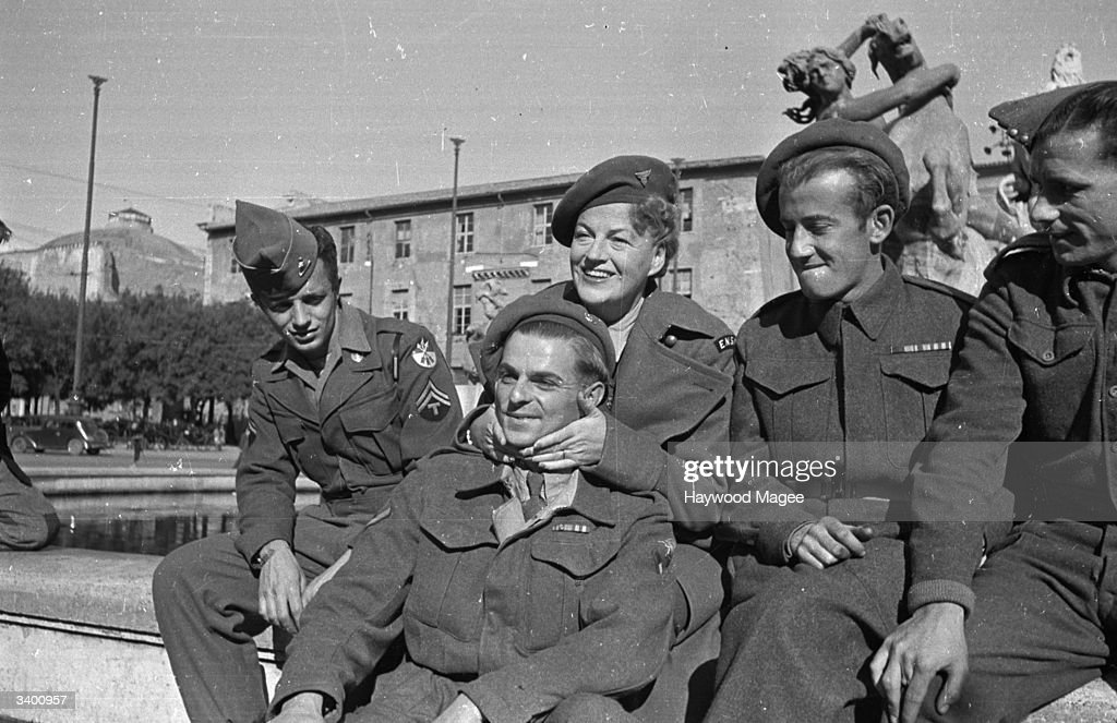 During an ENSA tour of Italy, singer and comedienne Gracie Fields (1898-1979) poses with members of the Allied Forces in Rome. Original Publication: Picture Post - 3048 - Gracie Fields Says Farewell To Rome - pub. 1945