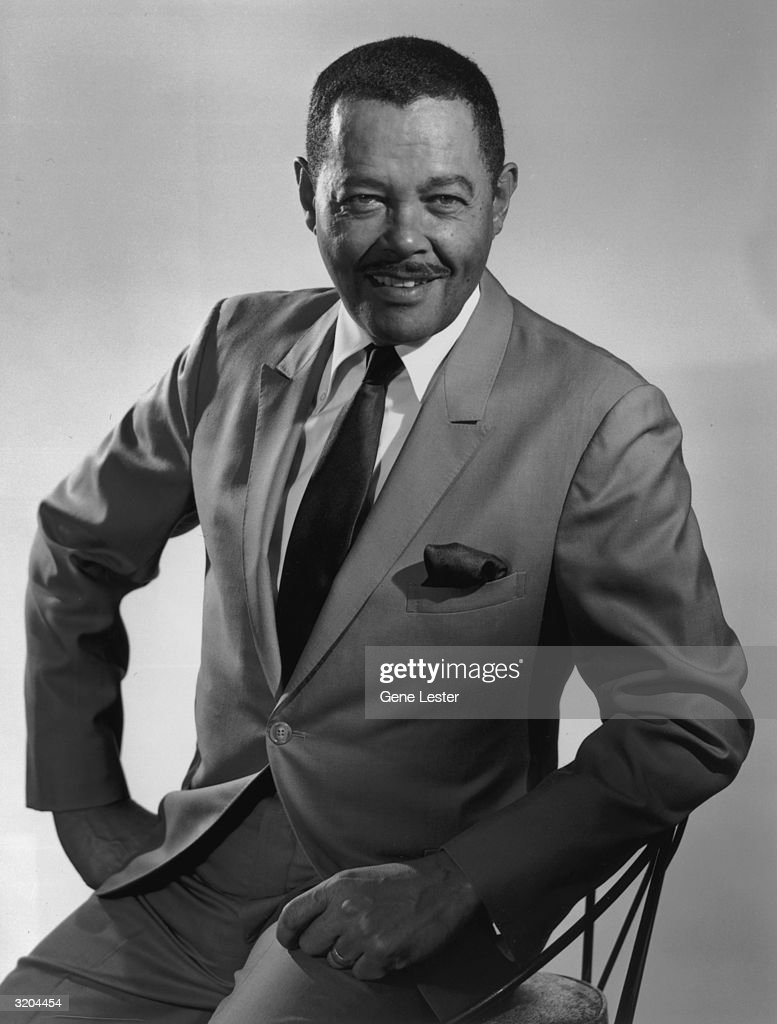 Studio portrait of American jazz and pop singer Billy Eckstine smiling while sitting with one hand to his hip in a suit and tie.