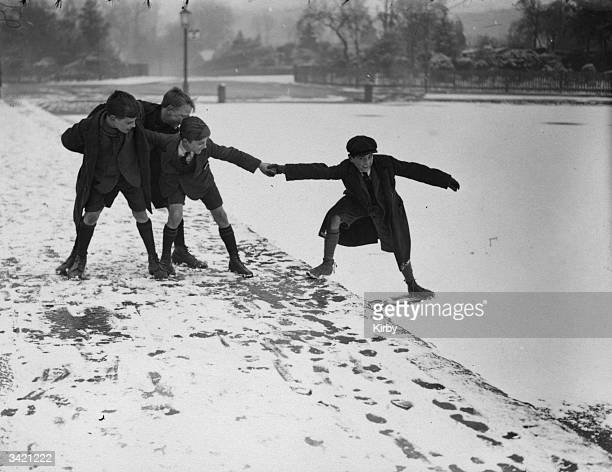 A schoolboy testing the ice on a lake on Hampstead Heath London