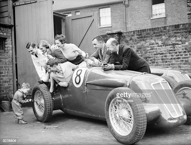 Two year old Bunny Almack making an adjustment to his fathers sports car while he and other members of the British Suicide stunt team Squad watch in...