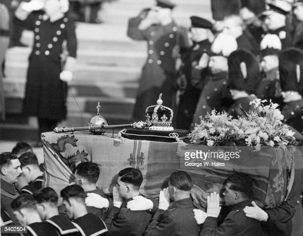 The coffin of George VI draped with the royal standard being carried by soldiers On the top are symbols of royalty a crown sceptre and orb