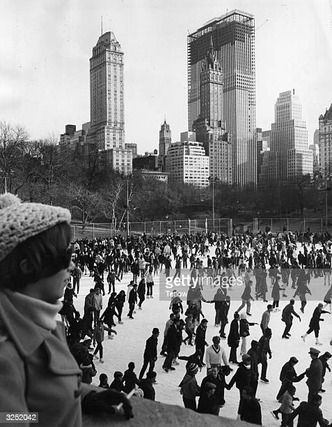 The crowed city ice rink in Central Park Manhattan The General Motors building is under construction in the background