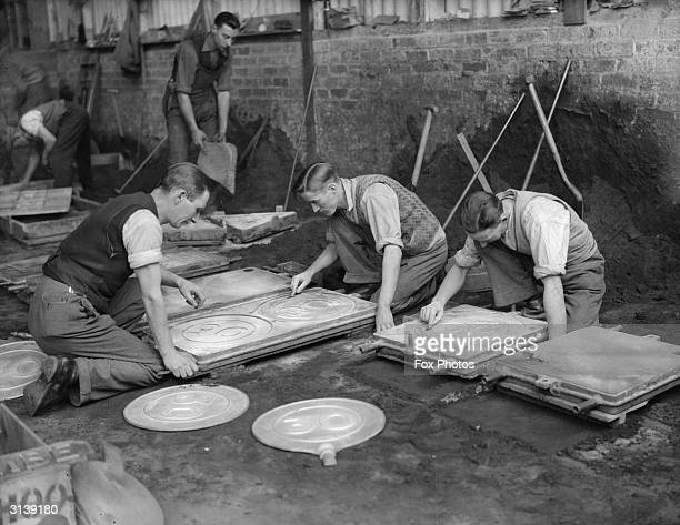 Men moulding the new 30mph limit road signs at the Royal Label Factory Stratford on Avon Warwickshire