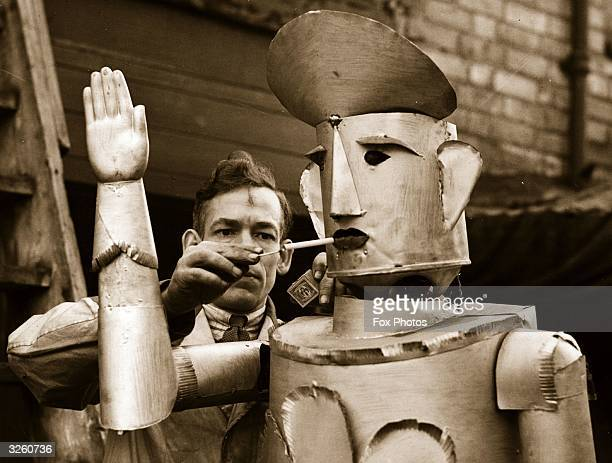 Mr Charles Lawson an electrical engineer of Kettering lights his robot's cigarette