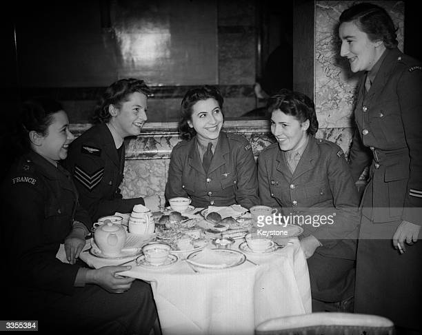 Madame Mathieu leader of the French ATS joining members of the corps and an English WAAF member at a 'Free France' teaparty reunion held at the Savoy...