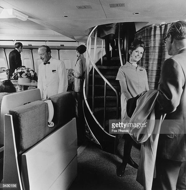 A BOAC air hostess greets a passenger in front of a spiral staircase which leads to the upper deck lounge in a Boeing 747 Monarch widecabin jet...