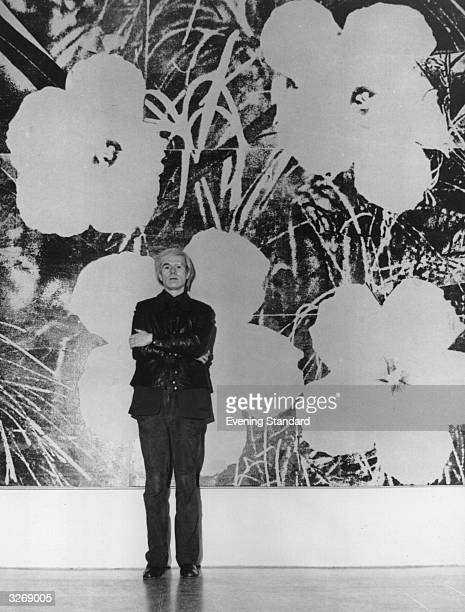 American popartist and film maker Andy Warhol standing in front of one of his large silk screen paintings of flowers