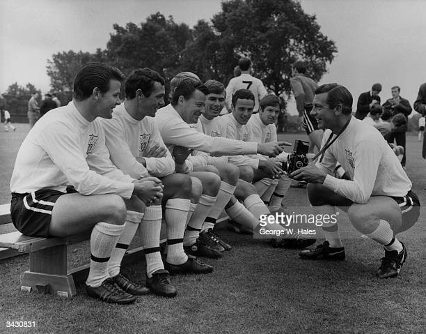 Fulham and England footballer Johnny Haynes receiving some advice about photography from his teammate Johnny Byrne