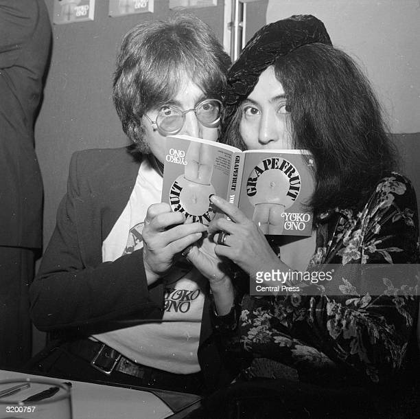 Japaneseborn artist Yoko Ono and her husband singer and songwriter John Lennon posing behind a copy of Ono's newlypublished photography book...