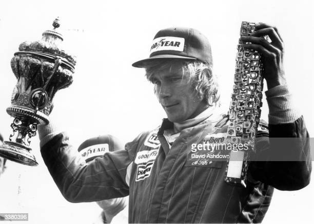 English motorracing driver James Hunt holding up the winners' trophies after victory in the British Grand Prix at Silverstone
