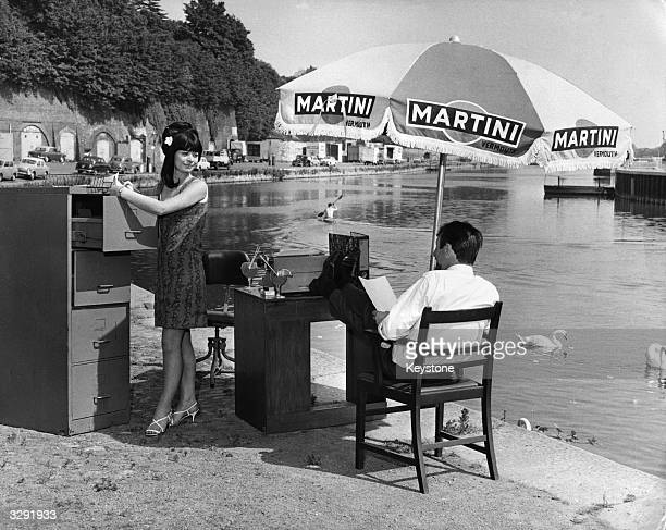 An office worker and his secretary move their office outside to beat the heatwave where the boss sits under a large 'Martini' umbrella Disc 1960's MA...