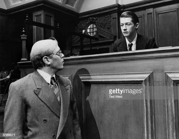 Richard Attenborough plays serial killer John Reginald Christie opposite actor John Hurt as Timothy Evans in a courtroom scene from the Columbia film...