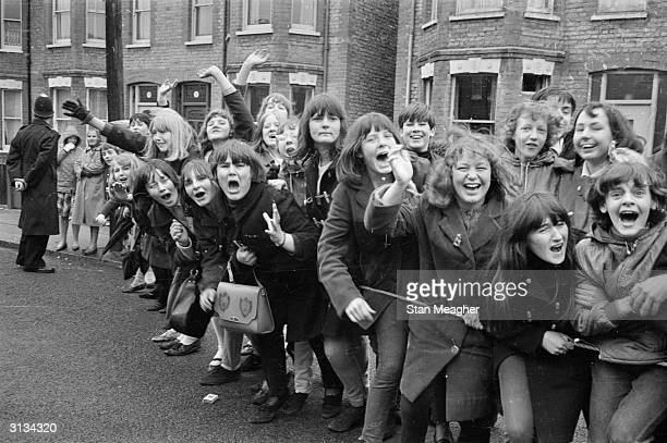 British police hold back excited young Beatles fans hoping for a glimpse of their musical heroes during the filming of the musical 'Help' on location...