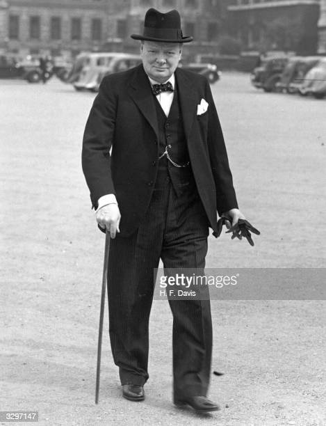 The British statesman Sir Winston Leonard Spencer Churchill the leader of the Coalition wartime government walking in the street with customary hat
