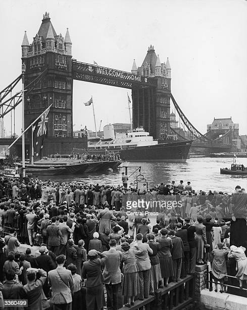 Crowds watching the Royal Yacht Britannia with the Queen and Duke of Edinburgh aboard as it passes under Tower Bridge on its way to Westminster London