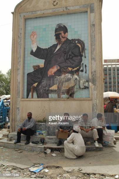 Iraqi men sit in front of a defaced mural of Saddam Hussein located on a roadside monument seen after the invasion of US forces in operation Shock...
