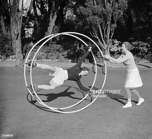 Tennis player Miss Mary Heeley in an exercise wheel being given a push by fellow athlete Miss Hardwick They are both taking part in a programme of...