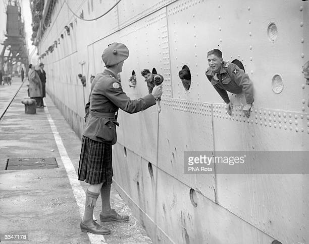 A BBC reporter wearing a kilt brings a microphone to the porthole of the SS Strathmore for men returning from the Second World War to broadcast...