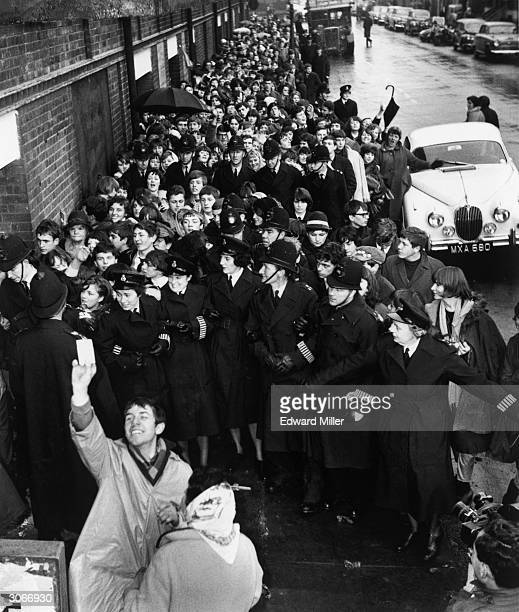 Police link arms to control the frenzied queue for Beatles tickets in Lewisham south London Many fans had queued overnight in the pouring rain for...