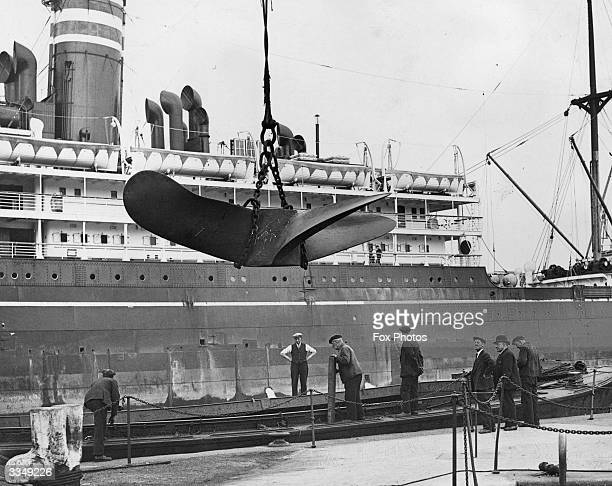 A propeller being lifted at the Royal Albert Docks London The SS Tuscan Star is in the background