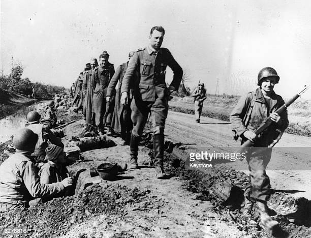 A line of captured Nazi prisoners led by a beaming American marches past the foxhole of American infantrymen in the Carroceto area near Naples