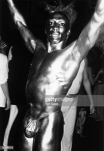 A dancer covered in metallic paint and wearing only a Gstring raises his arms at the reopening of Studio 54 New York City