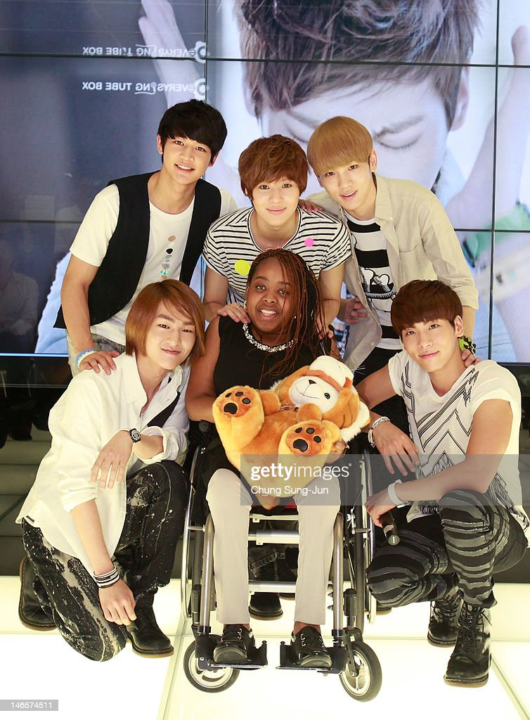 15-year old American girl Donica Streling smiles with members of SHINee at SM Entertainment head office on June 20, 2012 in Seoul, South Korea. Donica, diagnosed with Charcot-Marie-Tooth disease, visited Seoul, South Korea to meet her favorite K-pop groups SHINee and Super Junior after finding hope in listening to Korean pop.