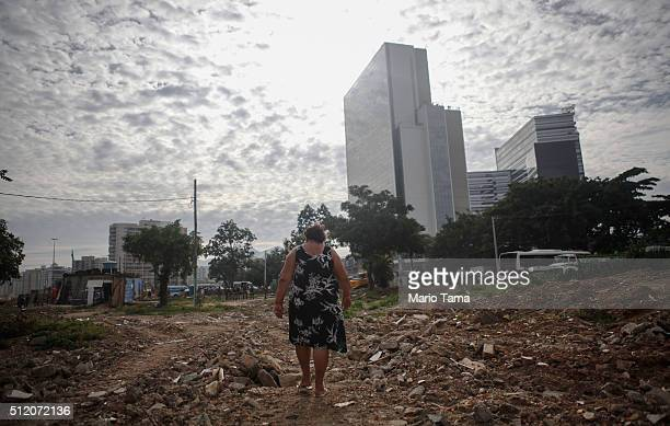 15year resident Cesara Araujo Lopes walks back to her home in the mostly demolished Vila Autodromo favela community with new Olympic Park structures...