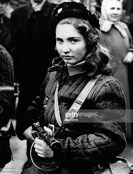A 15yearold Hungarian girl carries a machine gun in Budapest during the anticommunist revolution in Hungary