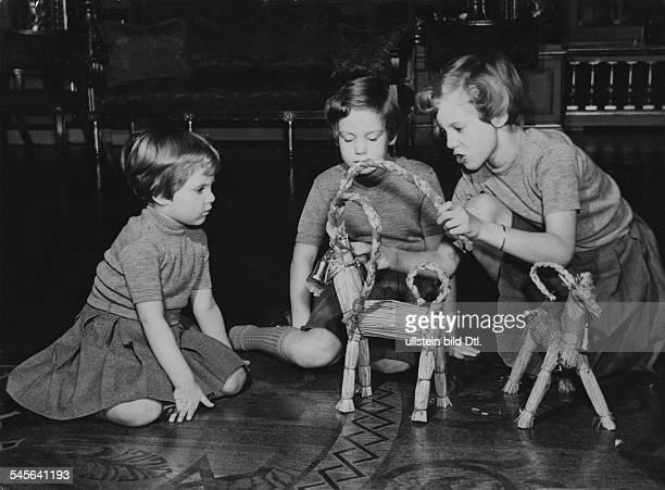 *Prinzessin Königin von Dänemark seit 1972mit ihren Schwestern Anne und Benedikte beim Spielen mit schwedischen aus Stroh geflochtenen Julböcken 1951