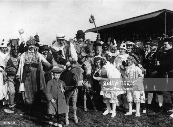 Music hall artists Joe Elvin and Harry Champion parade the Customs House football ground on donkeys at a charity football match